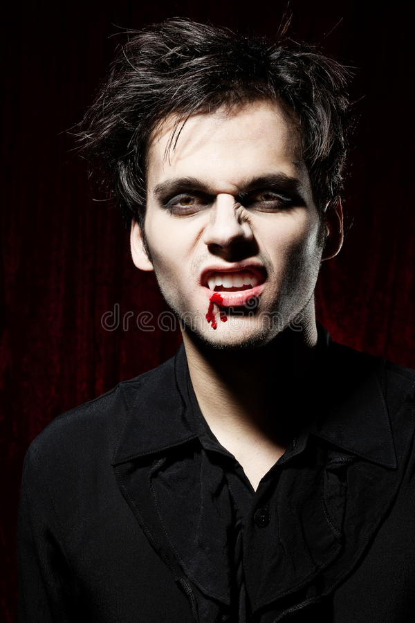 Portret van een mannelijke vampier die zijn tanden toont stock afbeeldingen