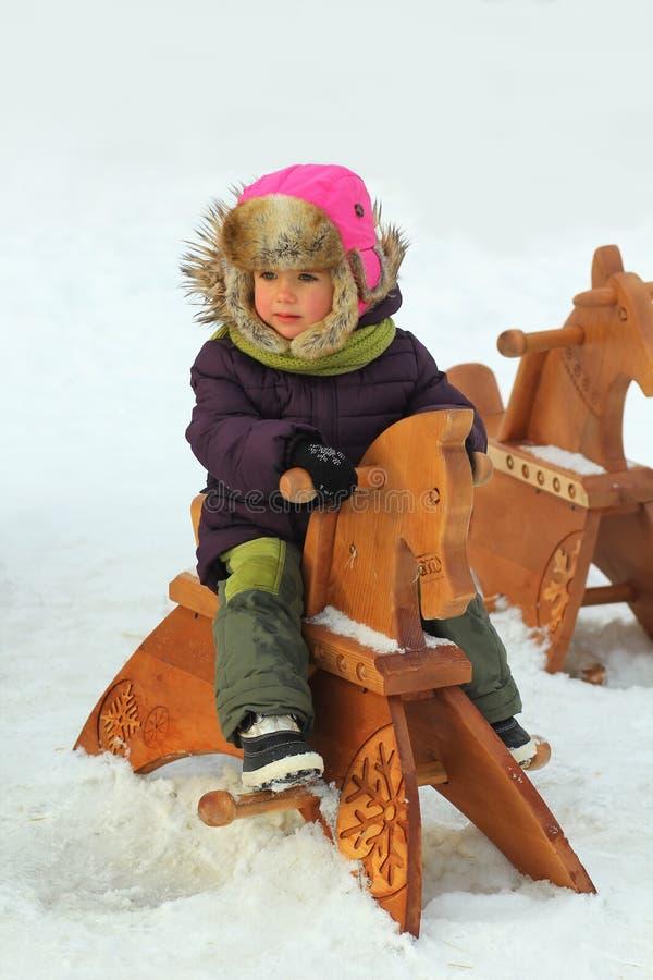 Portret van een meisje van de drie éénjarigenpeuter in de winterkleren op een houten paard op speelplaats royalty-vrije stock foto