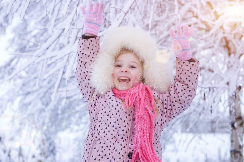 Portret van een meisje in de winter met de zon in een bonthoed stock foto