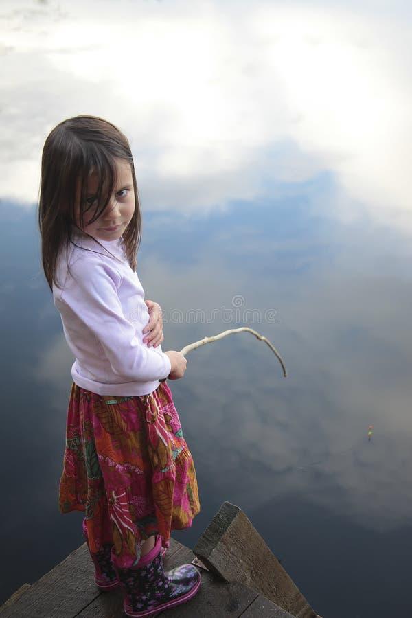 Portret van een meisje die in meer vissen die op de hemel wijzen royalty-vrije stock afbeelding