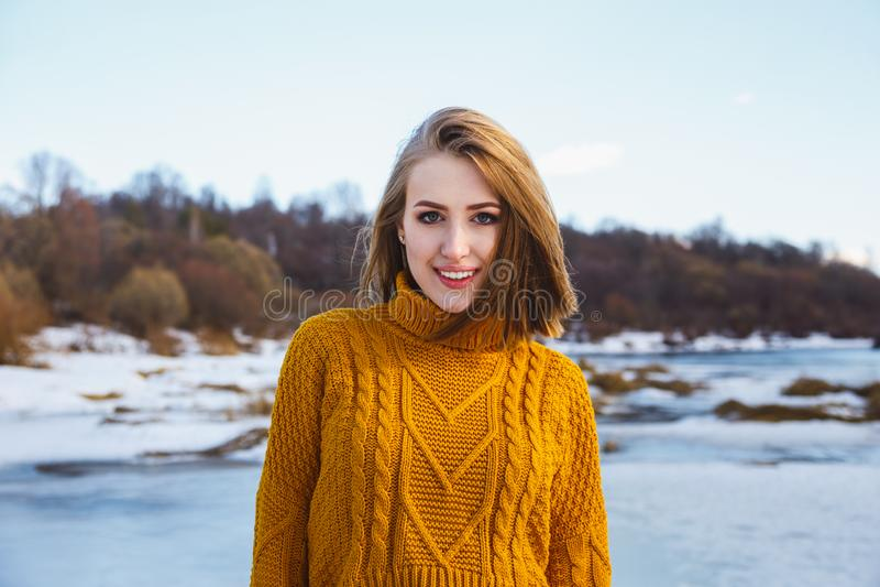 Portret van een meisje in een gele sweater en kort haar tegen een blauw hemel en de winterbos royalty-vrije stock foto's