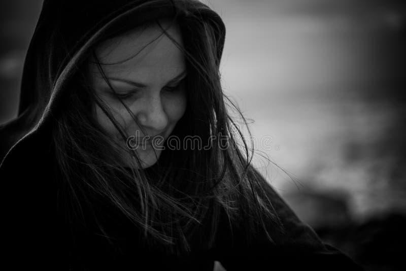 Portret van een meisje met winderig zwart haar in een kap, gesloten ogen en het glimlachen, bnw foto royalty-vrije stock afbeelding