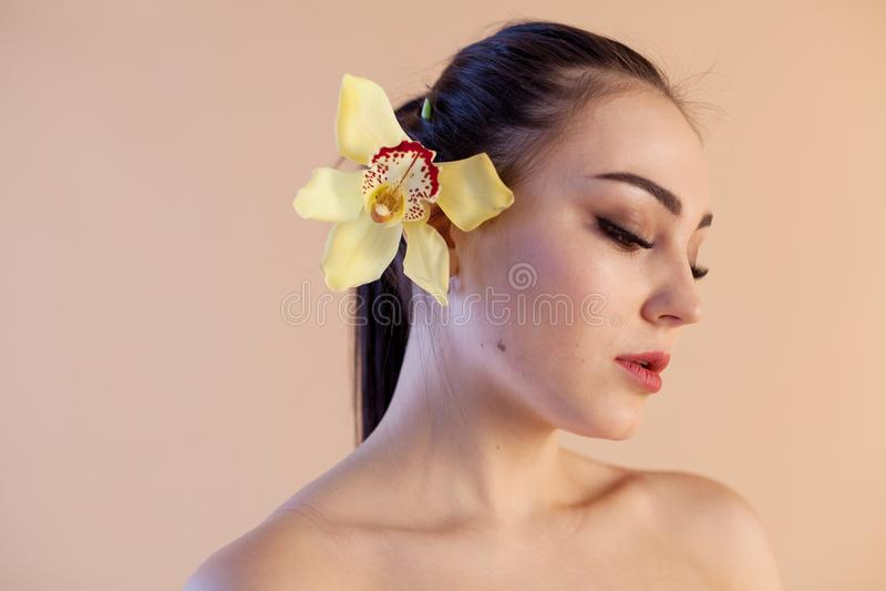 Portret van een meisje met een zorg van de bloemorchid Spa huid stock foto