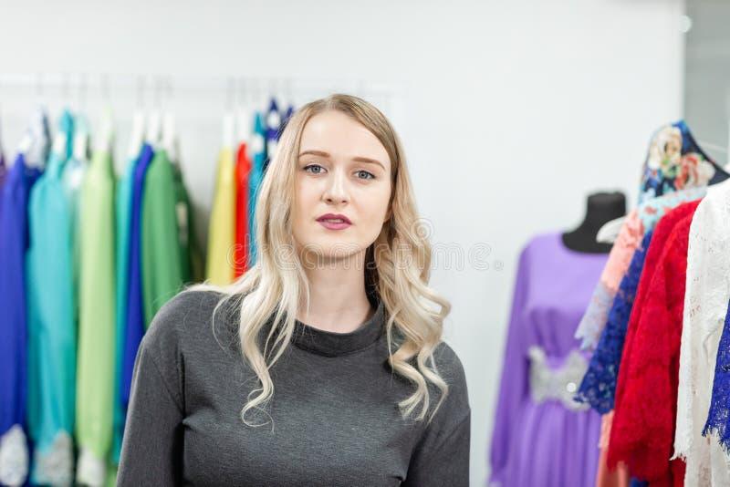 Portret van een meisje op de achtergrond van kleren op hangers in de kledingsopslag Gelukkige jonge vrouw die kleren kiest royalty-vrije stock afbeeldingen