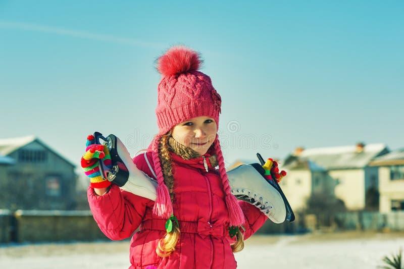 Portret van een meisje op de straat Een gelukkig kind gaat naar de piste stock fotografie
