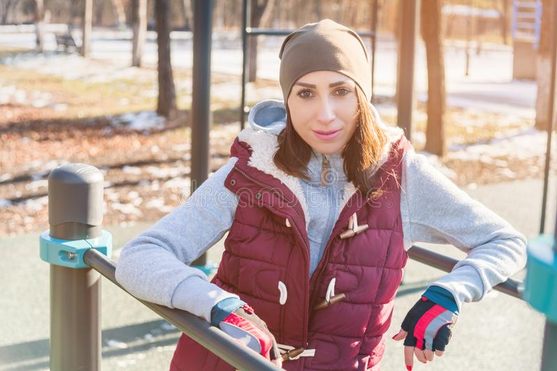 Portret van een meisjesatleet in een hoed met handschoenen en een warm vest naast een trainingspeelplaats in openlucht in de wint stock fotografie