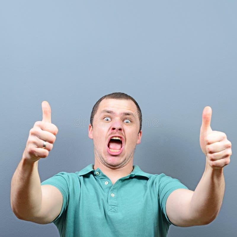 Portret van een mens die duim met lege ruimte boven zijn hoofd tonen tegen grijze achtergrond royalty-vrije stock foto's