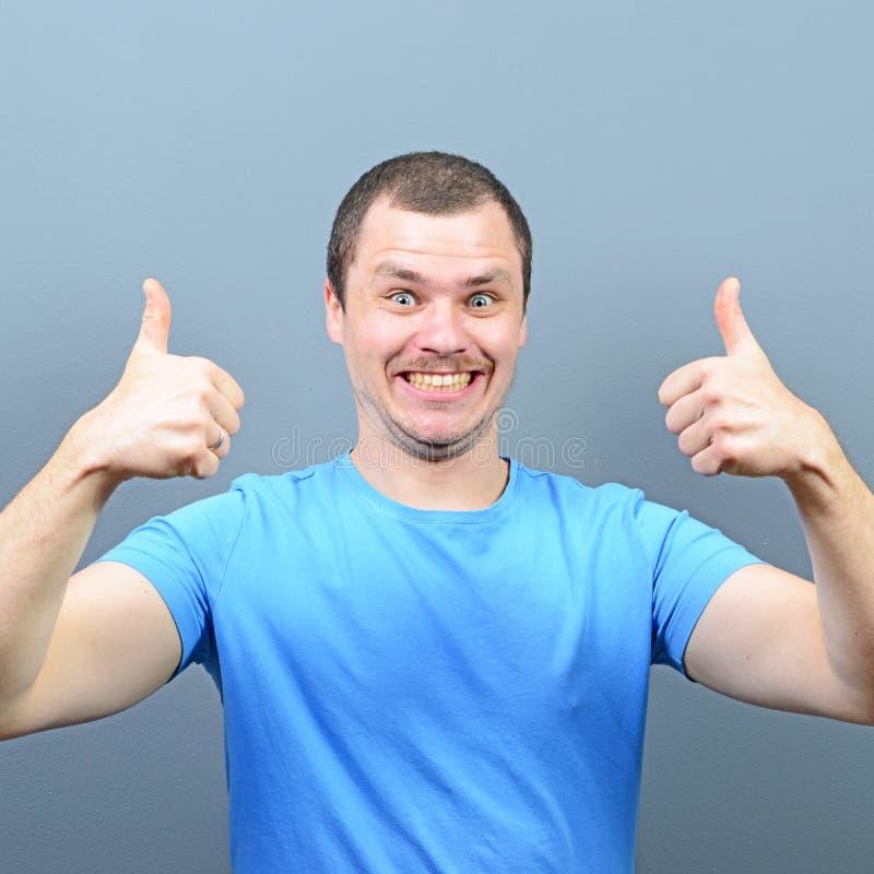 Portret van een mens die duim of o.k. teken tonen tegen grijze achtergrond stock foto