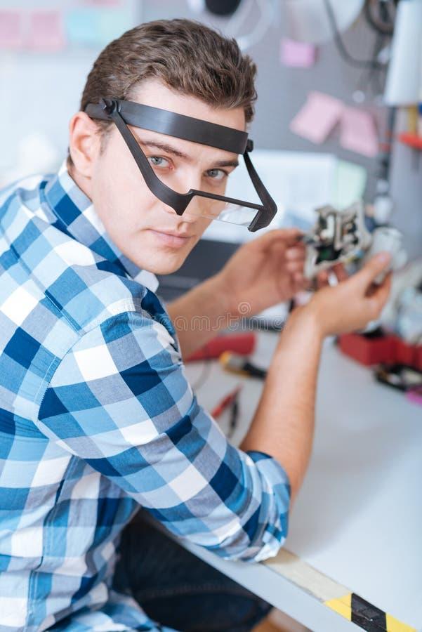 Portret van een mens die het mechanisme van de hommelcamera herstellen stock fotografie