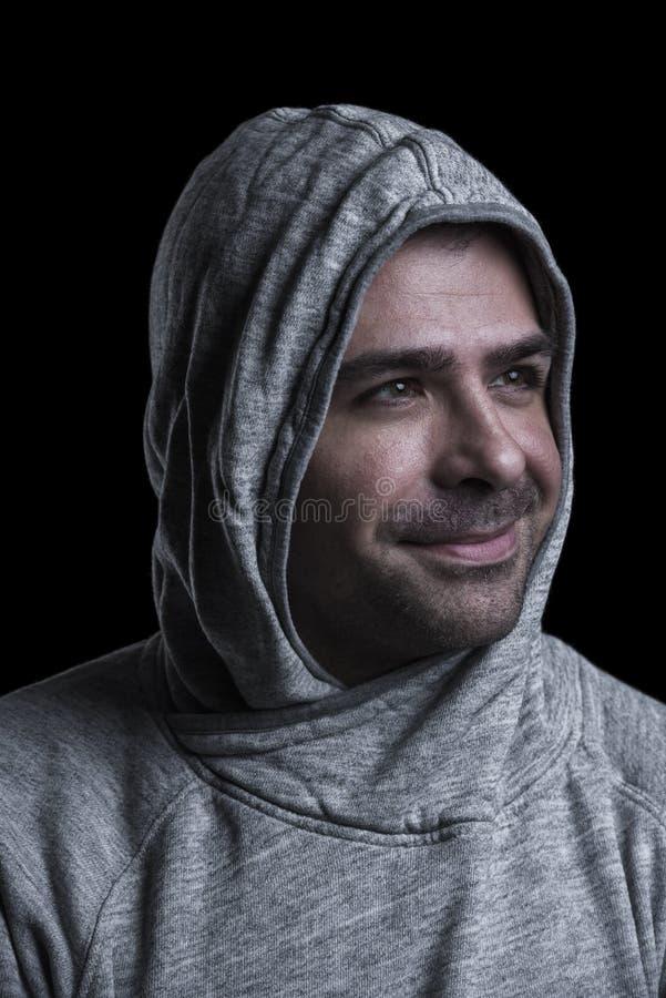 Portret van een mens die in kap zijdelings kijken Zwarte achtergrond stock afbeelding