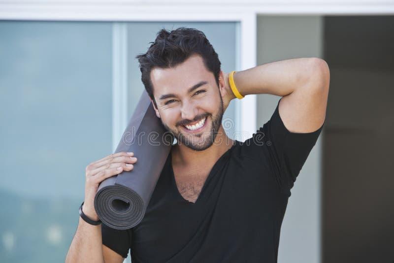 Portret van een mens het glimlachen mat van de holdingsyoga stock fotografie