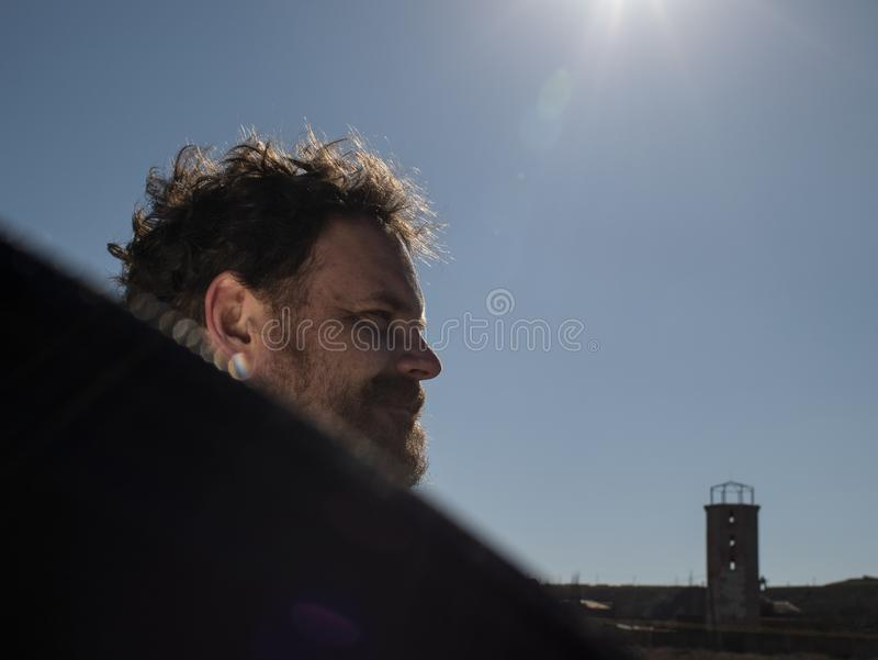 Portret van een mens met een baard en een snor die een reflector voor de zon houden stock foto