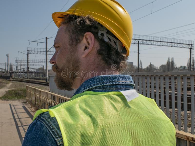 Portret van een mens met een baard en snor in een helm tegen de achtergrond van spoorwegspoor Spoorwegarbeider royalty-vrije stock afbeelding
