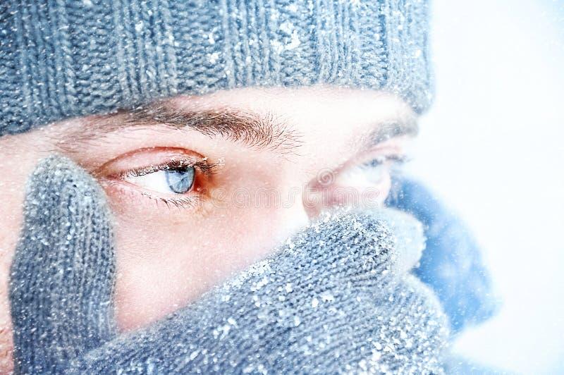 Portret van een mens met blauwe ogen tegen een achtergrond van dalende sneeuw Mooi sneeuwweer snowing Selectieve focu royalty-vrije stock afbeelding