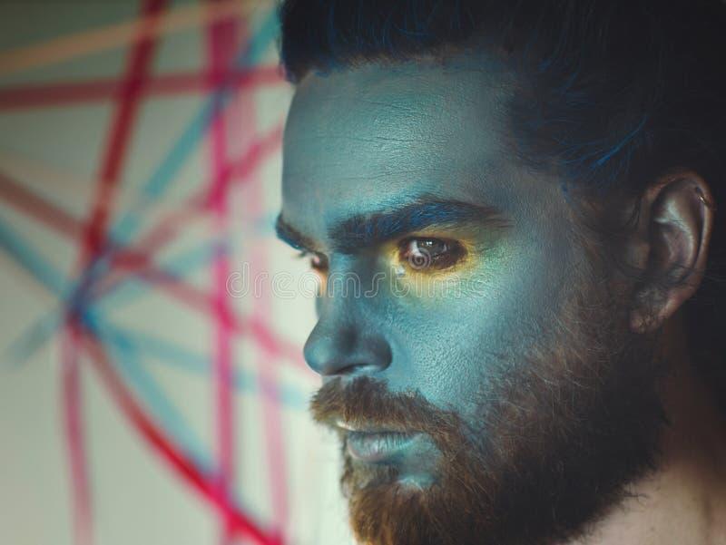 Portret van een mens met een blauwe samenstelling op zijn gezicht Stadiumsamenstelling, zoals een vreemdeling, fantasie stock foto's