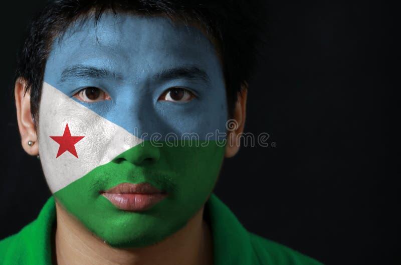 Portret van een mens met de vlag van Djibouti op zijn gezicht op zwarte achtergrond wordt geschilderd die royalty-vrije stock foto