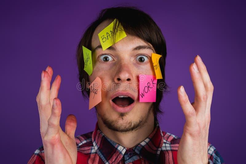 Portret van een mens met stickers op zijn die gezicht door verplichtingen, een mens met zijn handen omhoog in het gezicht in scho royalty-vrije stock foto's