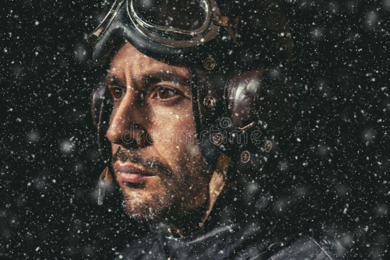 Portret van een mens met vliegeniershelm en beschermende brillen in zware sneeuw die de afstand onderzoeken stock afbeelding