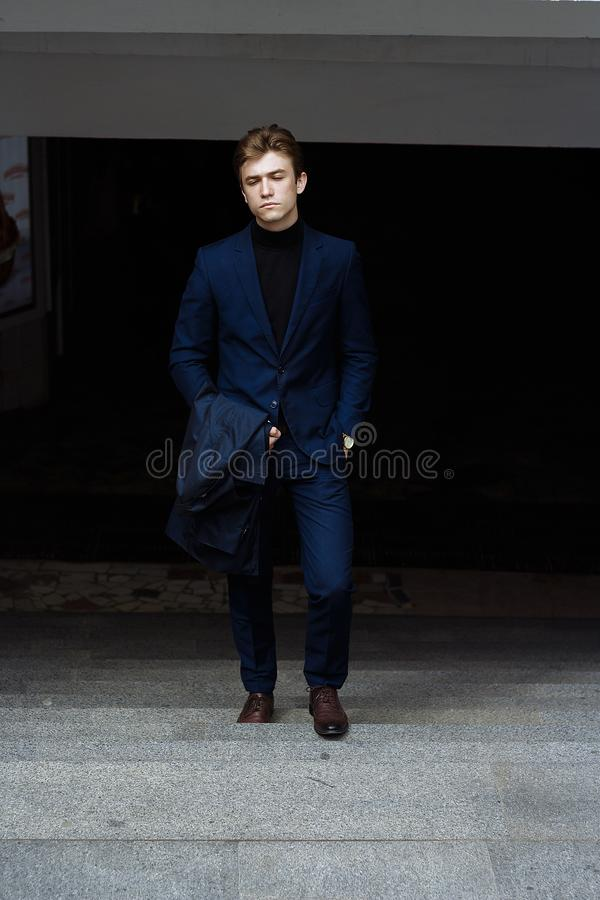portret van een mens, op de straat, in een kostuum en met een laag neemt op de stappen toe uit de duisternis, succes Zakenman Hor stock fotografie