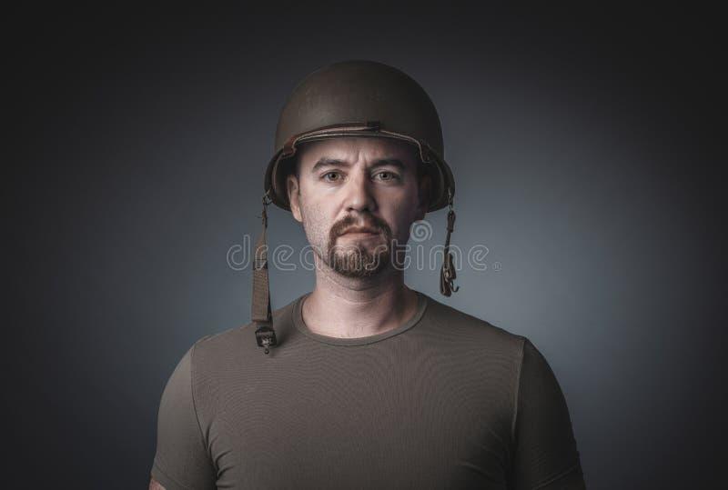 Portret van een mens in een t-shirt die de militaire helm van een militair dragen royalty-vrije stock foto