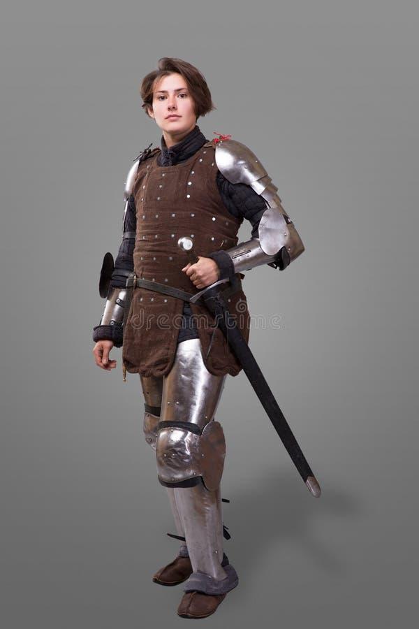 Portret van een middeleeuwse vrouwelijke ridder in pantser over grijze achtergrond stock foto's