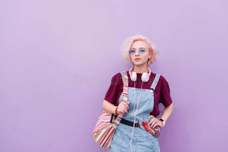 Portret van een modieus helder jong meisje met hoofdtelefoons, zonnebril en gekleurd haar op een purpere achtergrond stock fotografie