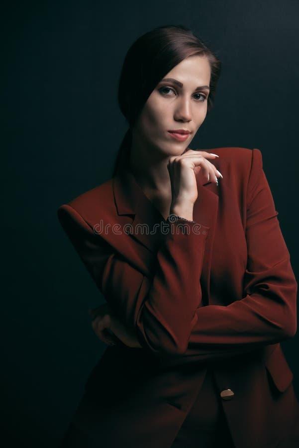 Portret van een modieuze bedrijfsvrouw in een jasje op een donkere achtergrond royalty-vrije stock foto's