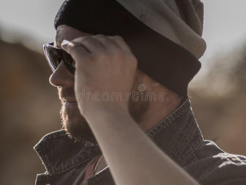Portret van een modieuze mens met een baard in een gebreide hoed en zonnebril royalty-vrije stock foto's