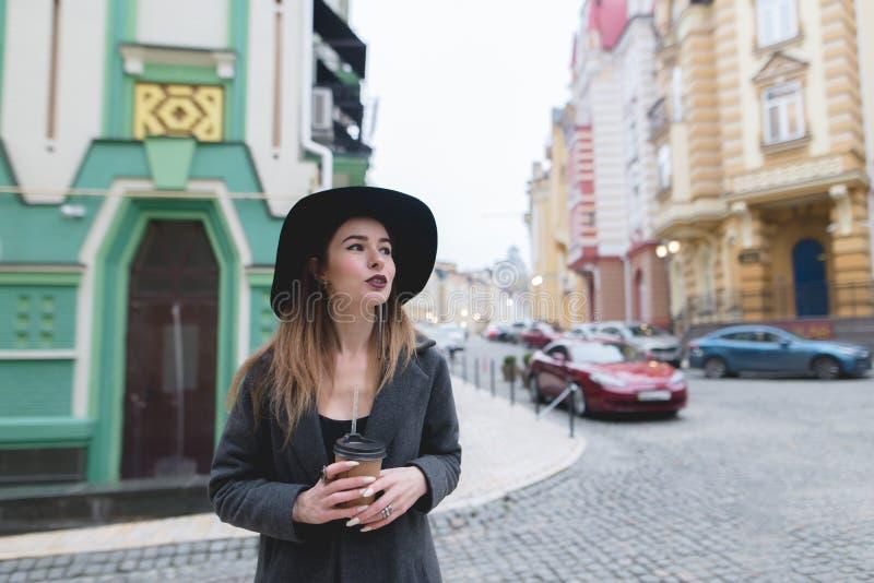 Portret van een modieuze mooie vrouw met een kop van koffie ter beschikking tegen een mooie stad royalty-vrije stock foto's