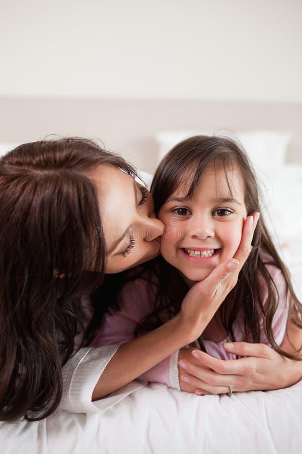 Portret van een moeder die haar dochter kussen royalty-vrije stock foto
