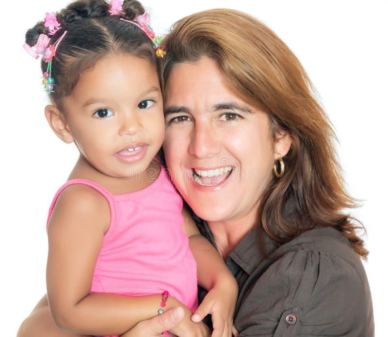 Portret van een moeder die haar kleine multiraciale dochter vervoeren stock afbeelding