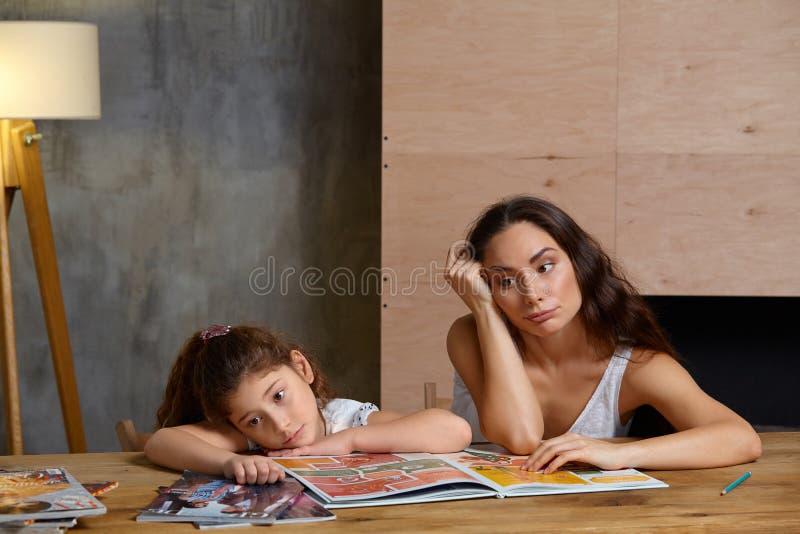 Portret van een moeder die haar kleine zoete en leuke dochter helpen om haar thuiswerk binnen te maken Gelukkige Familie royalty-vrije stock afbeelding