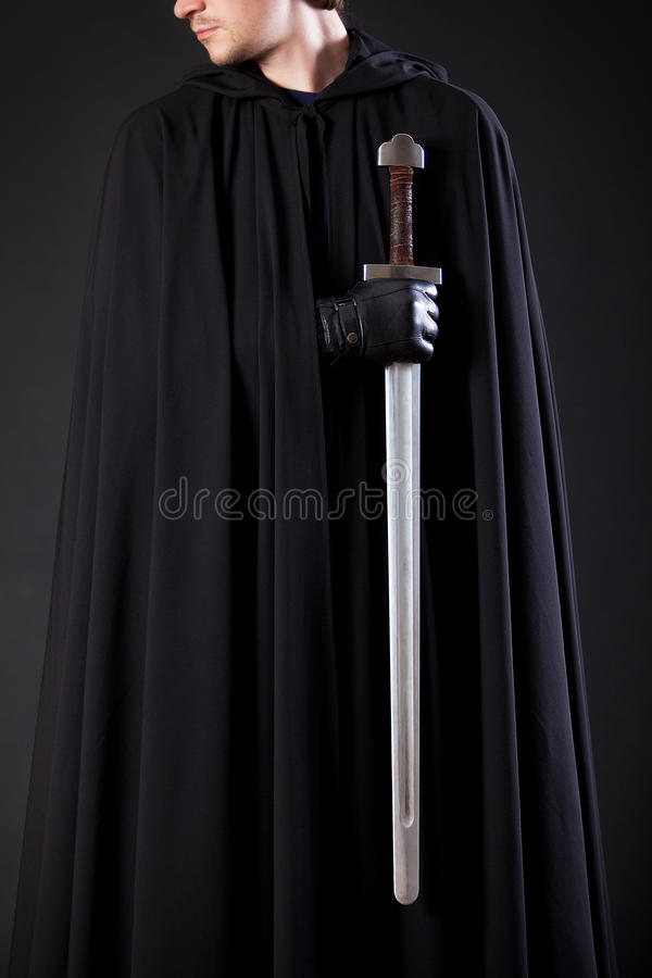 Portret van een moedige strijderszwerver in een zwart mantel en een zwaard ter beschikking royalty-vrije stock foto