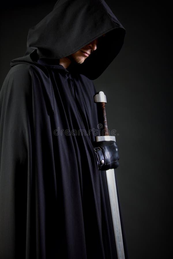 Portret van een moedige strijderszwerver in een zwart mantel en een zwaard ter beschikking stock foto's