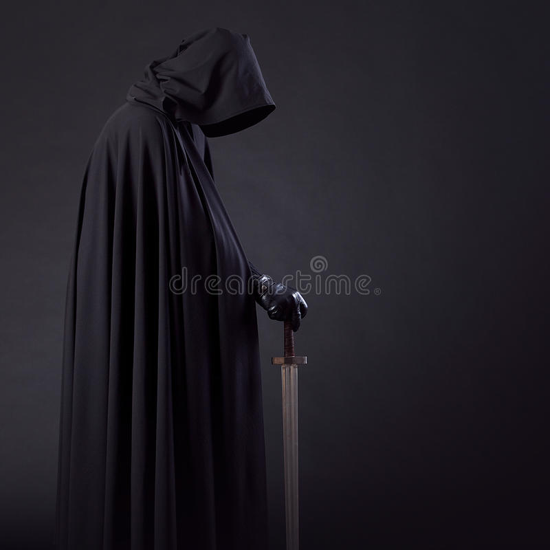 Portret van een moedige strijderszwerver in een zwart mantel en een zwaard ter beschikking royalty-vrije stock foto's
