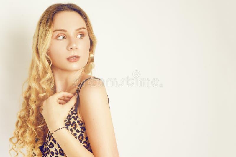 Portret van een mooi blonde met lang haar Meisje met gouden oorringen, namaakbijouterie, kleding met luipaarddruk Jong meisje met stock fotografie