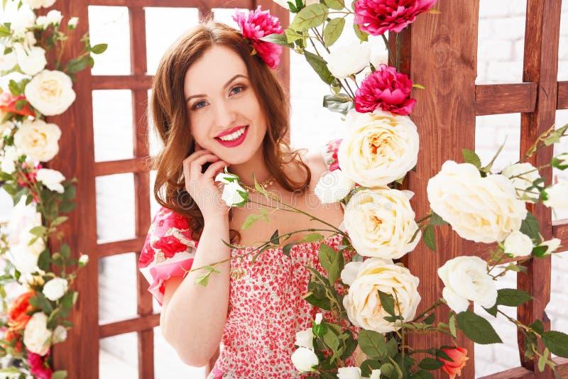 Portret van een mooi donkerbruin meisje in een de zomerkleding onder een bloemenboog royalty-vrije stock foto's