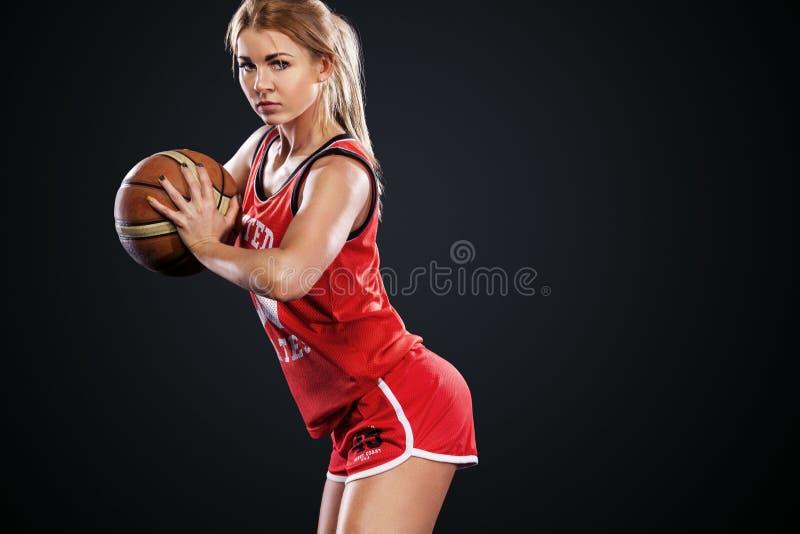 Portret van een mooi en sexy meisje met een basketbal in studio Sportconcept op zwarte achtergrond wordt geïsoleerd die stock fotografie