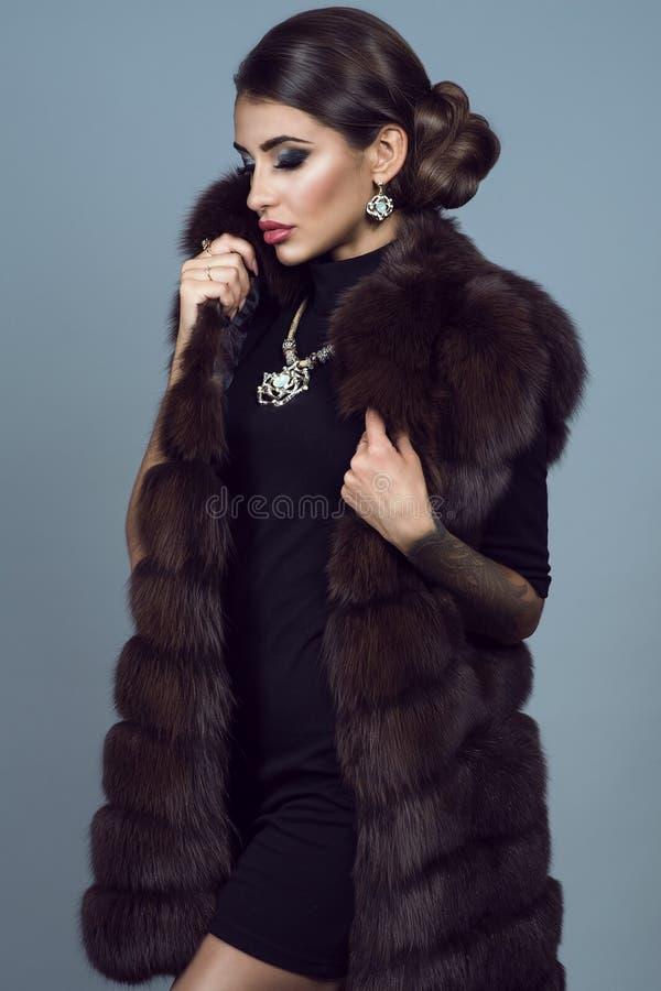 Portret van een mooi glam model dragend zwart kleding, een sabelmarterjasje en toebehoren stock foto's