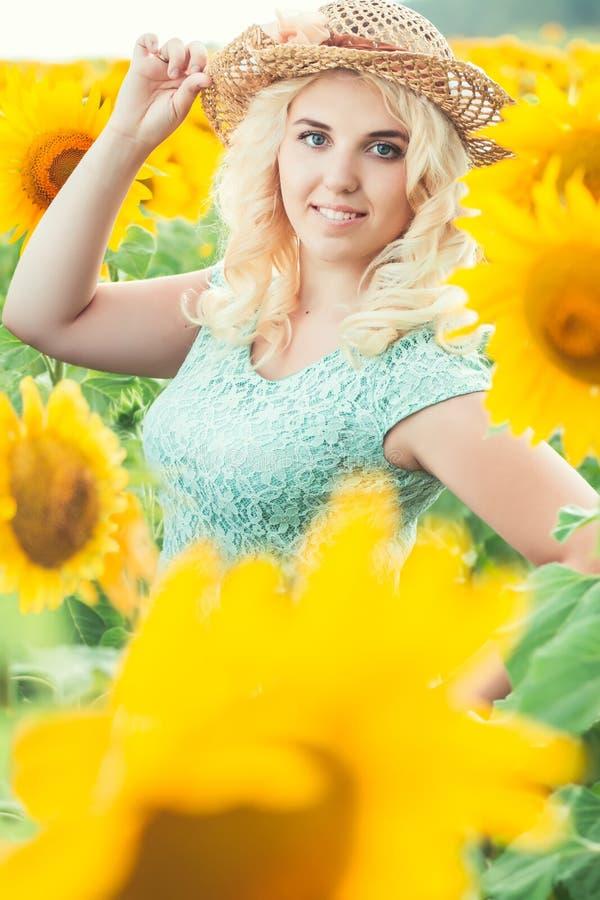 Portret van een mooi glimlachend blondemeisje in een strohoed in openlucht royalty-vrije stock afbeeldingen