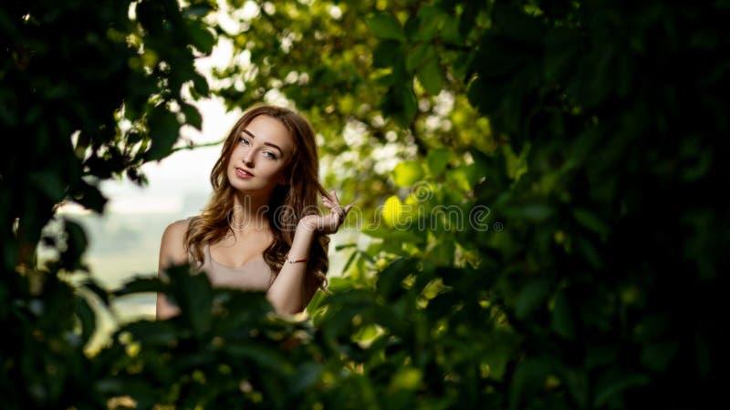Portret van een mooi glimlachend meisje in een de zomertuin, jonge vrouw in groen gebladerte stock fotografie