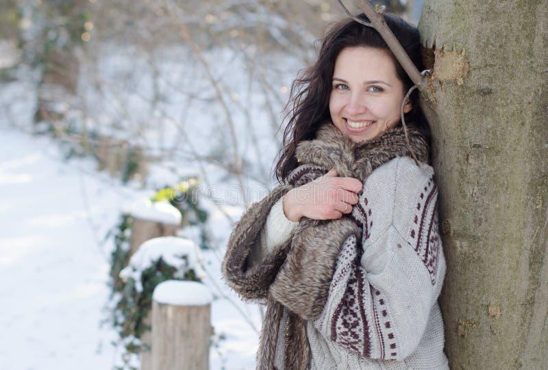 Portret van een mooi glimlachend meisje dichtbij de boom in de winter stock foto