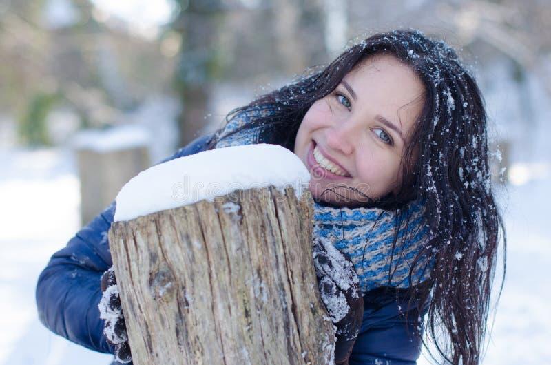 Portret van een mooi glimlachend meisje dichtbij de houten kolom in de winter stock fotografie