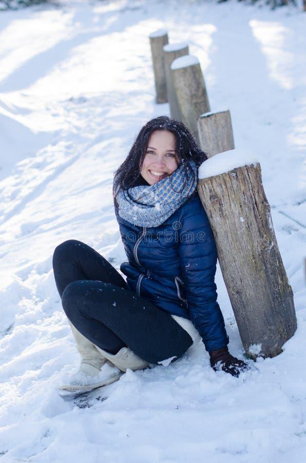 Portret van een mooi glimlachend meisje dichtbij de houten kolommen in de winter royalty-vrije stock fotografie