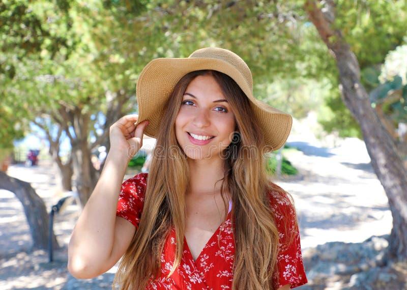 Portret van een mooi glimlachend meisje die hoed en rode kleding dragen die camera in openlucht bekijken stock afbeeldingen