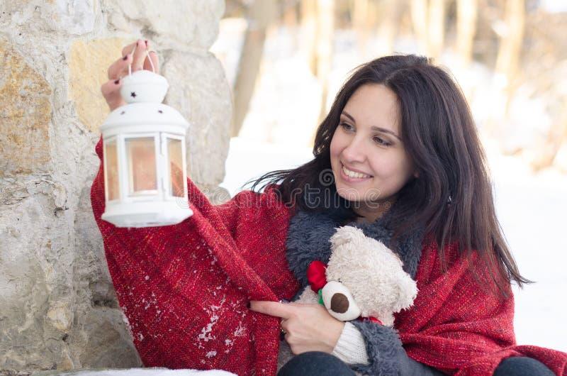Portret van een mooi glimlachend meisje met teddybeer en lamp in de winter royalty-vrije stock afbeelding