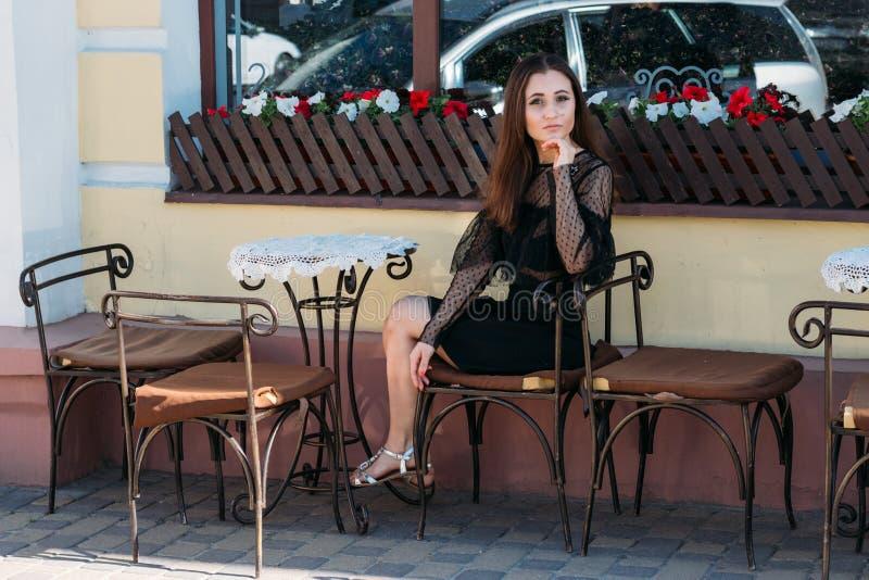 Portret van een mooi, jong, aantrekkelijk meisje dat op de straat in een koffie zit wachtend op ontbijt, de zomer, datum droom stock foto