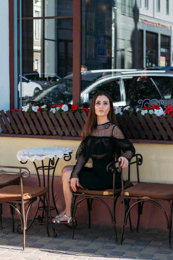 Portret van een mooi, jong, aantrekkelijk meisje dat op de straat in een koffie zit wachtend op ontbijt, de zomer, datum droom stock afbeelding