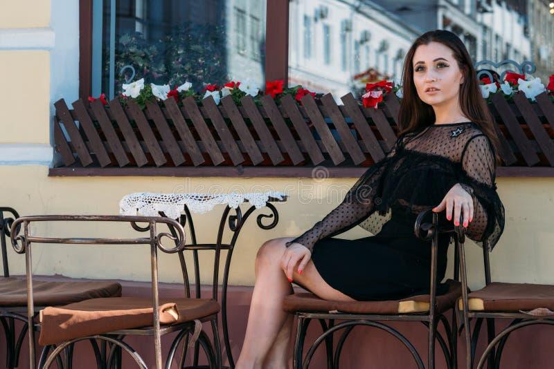Portret van een mooi, jong, aantrekkelijk meisje dat op de straat in een koffie zit wachtend op ontbijt, de zomer, datum droom royalty-vrije stock foto's