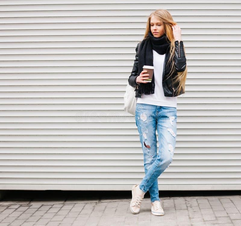 Portret van een mooi jong blondemeisje met het lange haar stellen op een straat met koffie en een rugzak Openlucht, warme kleur royalty-vrije stock afbeelding